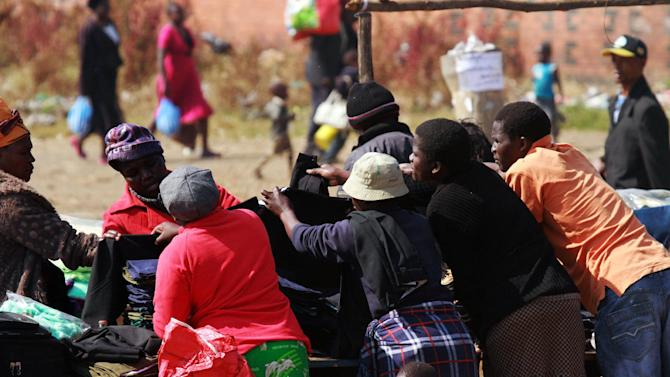 Traders sell clothing products to customers walking past their stalls in Mbare, Harare, Thursday Aug. 8, 2013. Zimbabwean President elect, Robert Mugabe, 89, received the mandate to rule the country for the next five years after receiving more than 60 percent of the vote beating his main challenger Morgan Tsvangirai who has declared the election null and void and vowed to fight the outcome in courts. (AP Photo/Tsvangirayi Mukwazhi)