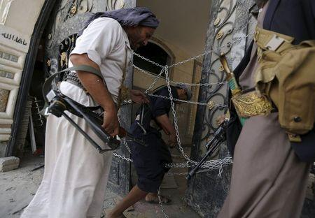 Guards walk through a damaged gate of the house of Brigadier Khaled al-Anduli, an army commander loyal to the Houthi movement, after it was hit by Saudi-led air strikes in Yemen's capital Sanaa