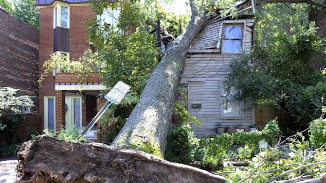 A downed tree crushes an old home on Dent Street in the Georgetown section of  Washington, Sunday, Aug. 28, 2011, brought down by rain and wind from Hurricane Irene.  (AP Photo/Cliff Owen)