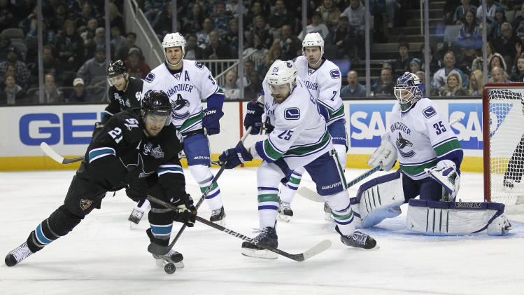 San Jose Sharks left wing T.J. Galiardi (21) battles for the puck in front of the goal against Vancouver Canucks center Andrew Ebbett (25) as Canucks goalie Cory Schneider (35) watches during the first period of an NHL hockey game in San Jose, Calif., Sunday, Jan. 27, 2013. (AP Photo/Tony Avelar)