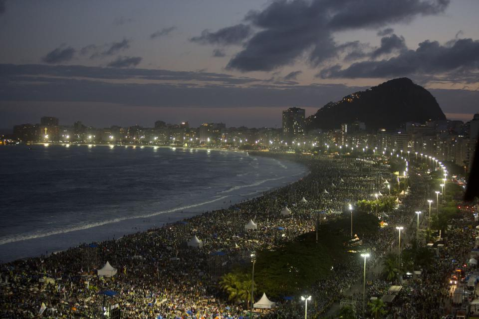 Pilgrims and residents gather on Copacabana beach before the arrival of Pope Francis for World Youth Day in Rio de Janeiro, Brazil, Saturday, July 27, 2013. Francis will preside over an evening vigil service on Copacabana beach that is expected to draw more than 1 million young people. (AP Photo/Andre Penner)