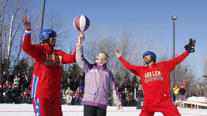 The Harlem Globetrotters seen at Globetrotters Play Basketball On Ice on Monday, January 7th, 2013 in Portage, Michigan. Harlem Globetrotter Scooter Christensen (l) spins the ball on the finger of 10-year old Emilee Bogda of Kalamazoo, MI. Handles Franklin (r) leads the cheers.  The Globetrotters took to the ice to help fill the void of the cancelled Winter Classic in Michigan. (Photo by William Pugliano/Invision for Globetrotters/AP Images)