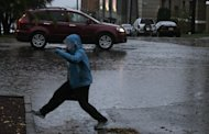 A pedestrian navigates around standing water, Monday, Nov. 19, 2012, at an intersection in Tacoma, Wash. Wet and windy weather with mountain snow will continue this week in Washington, forecasters said. (AP Photo/Ted S. Warren)