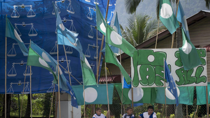Schoolchildren sit along a road side after school as National Front and Islamic Party flags are on display ahead of the upcoming general elections in Ipoh, Malaysia, Tuesday, April 2, 2013. (AP Photo/Vincent Thian)