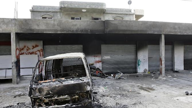 This picture taken on Monday, Feb. 24, 2014 shows the burned car of Hisham al-Mughayar, 45, the father of the suicide bomber Nidal al-Mughayar, which was torched as well as the family's grocery shop and four vehicles by angry residents after the news spread in the village that Nidal was one of the two suicide attackers who carried out an attack in Beirut near the Iranian culture center, in the southern village of Bisariyeh, Lebanon. Nidal al-Mughayar renewed his travel document last year and told his family he will be leaving Lebanon to settle in Venezuela where there are more opportunities but it turned out later that the young Palestinian man called his family from Syria and it was only then that they knew he has joined jihadis fighting to overthrow President Bashar Assad's government. (AP Photo/Mohammed Zaatari)