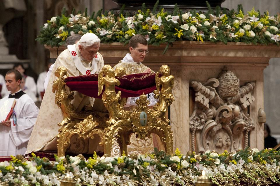 Pope Benedict XVI kneels in prayer as he celebrates Christmas Mass in St. Peter's Basilica at the Vatican, Saturday, Dec. 24, 2011. (AP Photo/Andrew Medichini)