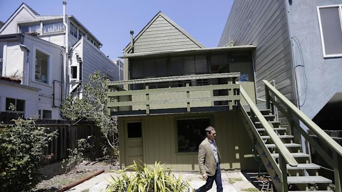 George Limperis, a realtor with Paragon Real Estate Group, walks in the backyard of a property in the Noe Valley neighborhood in San Francisco, Wednesday, July 30, 2014. In the souped-up world of San Francisco real estate, where the median selling price for homes and condominiums hit seven figures for the first time last month, the cool million that would fetch a mansion on a few acres elsewhere will now barely cover the cost of an 800-square foot starter home that needs work and may or may not include private parking. (AP Photo/Jeff Chiu)