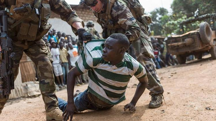 French soldiers arrest an alleged ex-seleka rebel denounced by inhabitants in the Combattant neighborhood near Bangui's airport, on December 9, 2013
