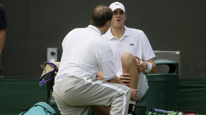 John Isner of the United States, right, is attended to before retiring injured from his Men's second round singles match against Adrian Mannarino of France at the All England Lawn Tennis Championships in Wimbledon, London, Wednesday, June 26, 2013. (AP Photo/Alastair Grant)