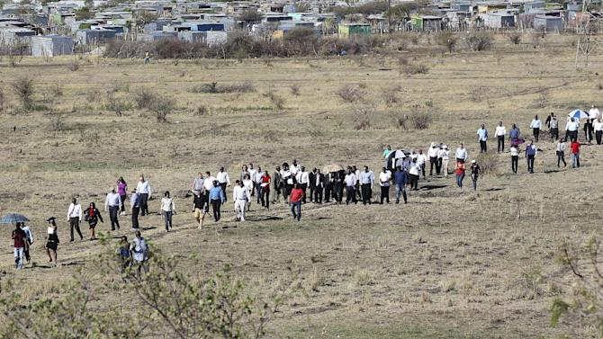 A large crowd follows retired judge Ian Farlam and his team as they inspect the area where the bodies of mine workers were found, after the shootings at Lonmin's platinum mine in Marikana near Rustenburg, South Africa, Monday, Oct. 1, 2012.  An official inquiry into the killings of dozens of people near a South African platinum mine began Monday even as labor unrest continued with workers at other mines as well as truck drivers continuing protests over pay. (AP Photo/Themba Hadebe)