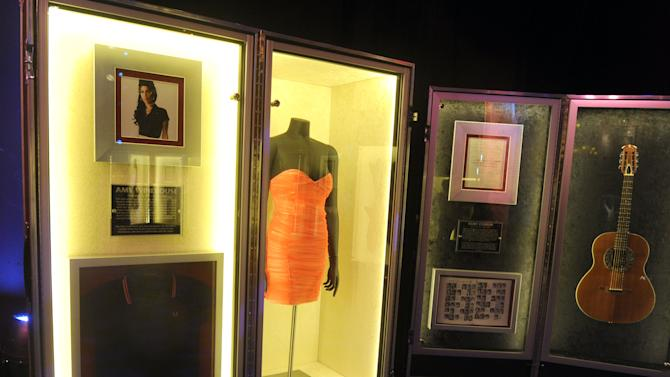 """A pink dress worn on stage by Amy Winehouse in 2008 is on display at Hard Rock International's traveling music memorabilia tour, """"Gone Too Soon, """" Wednesday, Feb. 13, 2013, at Hard Rock Cafe New York.  """"Gone Too Soon"""" pays tribute to music icons whose lives and career where tragically cut short and will be on tour at Hard Rock locations in the U.S. throughout 2013. (Photo by Diane Bondareff/Invision for Hard Rock International/AP Images)"""