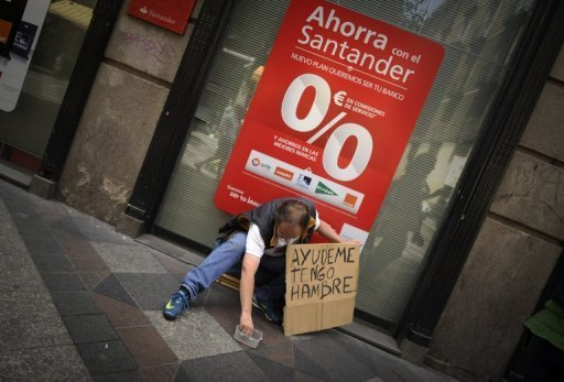 A man with a sign reading ''Help me, I am hungry'' asks for money in front of a bank in Madrid