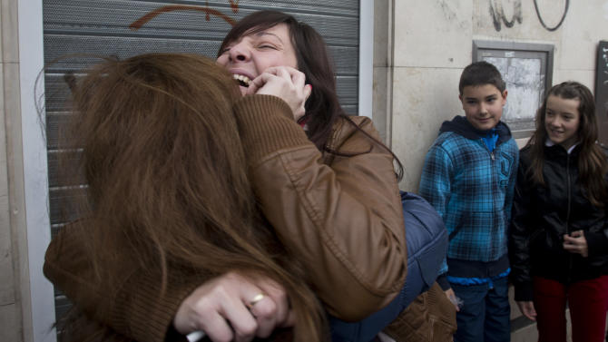 "Azahara, right, hugs her mother after winning the main Christmas lottery prize ""El Gordo"" (""The Fat One"") in Alcala de Henares, just outside of Madrid,  Saturday Dec. 22, 2012.  Lucky winners of Spain's cherished Christmas lottery, the world's richest,  celebrated Saturday, as initial indicators show more than a dozen locations where lucky tickets were sold, each picking up the maximum prize of euro 400,000 (US dlrs 529,840), and some thousands of tickets yielding smaller prizes. (AP Photo/Paul White)"