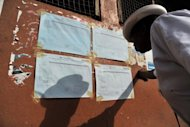 <p>A man checks results of the elections at a polling station in Freetown, on November 18. Sierra Leone is anxiously awaiting poll results in a high-stakes general election, with tensions erupting in a key eastern city as ruling party supporters celebrate positive early returns.</p>