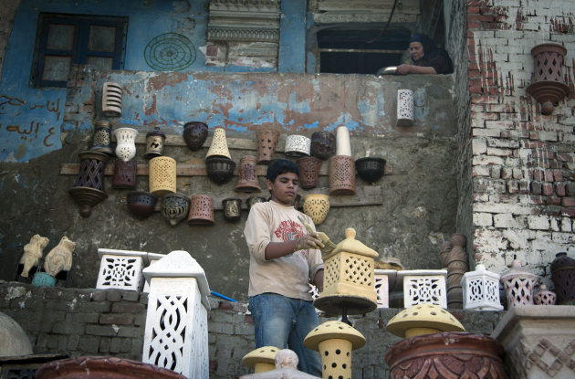 In this Oct. 18, 2012 photo, Ezzat, an Egyptian child paints clay pottery in front of his house in old Cairo, Egypt. The Egyptian government estimates that some 1.6 million minors work - almost 10 percent of population aged 17 or under, often in arduous conditions. Other experts put the number at nearly twice that. Some child labor activists worry that protections for children could be loosened further under the new constitution still being written. Earlier this month, the Egyptian Coalition for Children's Rights warned that early drafts of the document did not include as firm prohibitions on child labor as past constitutions.(AP Photo/Khalil Hamra)