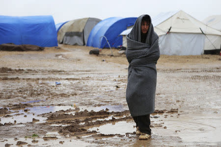 A refugee from the minority Yazidi sect wraps himself with a blanket as he stands on a muddy path during wintry weather at Nowruz refugee camp in Qamishli