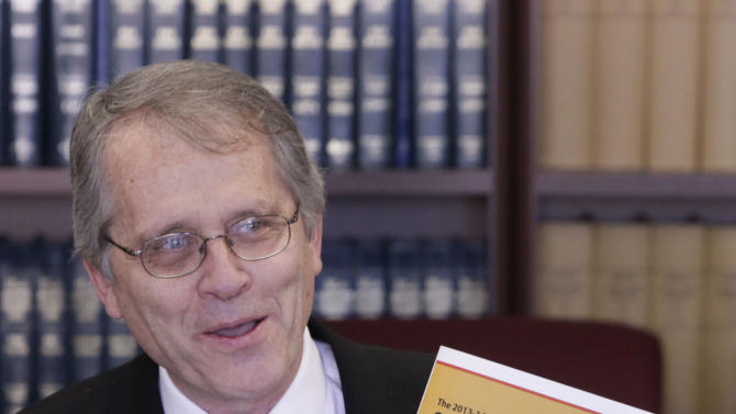 Legislative Analyst Mac Taylor displays a copy of his offices report on the state's fiscal outlook during a news conference in Sacramento, Calif., Wednesday, Nov. 14, 2012.  Taylor projected a much smaller deficit of $1.9 billion through the end of 20123 fiscal year in July 2013, as compared with the $15.7 billion deficit lawmakers faced earlier this year. (AP Photo/Rich Pedroncelli)