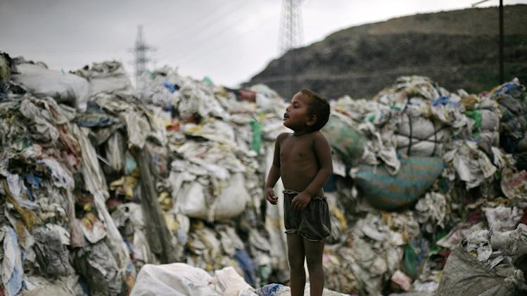 In this Sept. 7, 2012 photo, a ragpicker's child tries to sneak from above a heap of segregated garbage at an impoverished neighborhood of ragpickers on the outskirts of New Delhi, India. Those whose survival depends on this gray market in trash fear their lives are about to be upended. Because where they see money in those mountains of garbage, the New Delhi government sees electricity. Desperate for cheap energy, the Delhi government is experimenting with power plants fueled by garbage. One plant is now running on a trial basis and two more are under construction. (AP Photo/Altaf Qadri)