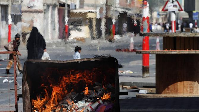 "Bahraini anti-government protesters look for riot police by a burned dumpster in Malkiya village, Bahrain, Thursday, March 14, 2013. Protests and clashes erupted in opposition areas nationwide Thursday with government opponents observing a ""Dignity Strike"" blocking roads, closing shops, protesting and staying home from work and school, called by the more radical February 14 youth group. (AP Photo/Hasan Jamali)"