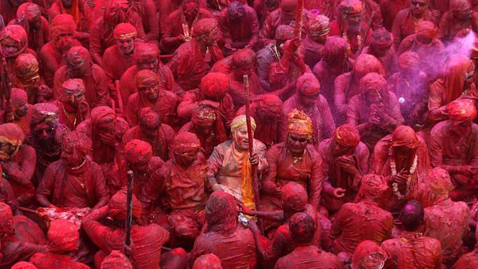 Indian Hindu devotees smeared with colors sing at the Nandagram temple, famous for Lord Krishna and his brother Balram, during Lathmar holy festival, in Nandgaon, India , Friday, March 22, 2013. During Lathmar Holi the women of Nandgaon, the hometown of Krishna, beat the men from Barsana, the legendary hometown of Radha, consort of Hindu God Krishna, with wooden sticks in response to their teasing as they depart the town. (AP Photo / Manish Swarup)