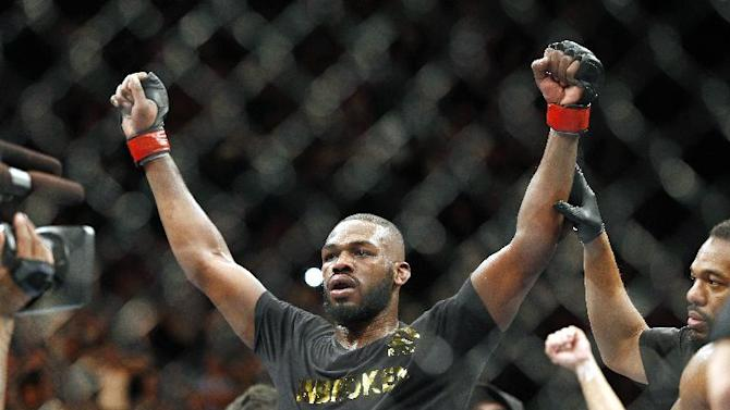 FILE - This Jan. 3, 2015, file photo shows Jon Jones celebrates after defeating Daniel Cormier during their light heavyweight title mixed martial arts bout in Las Vegas. Albuquerque police were searching for UFC light heavyweight champion Jones on Sunday night, April 26, 2015, in connection with a hit-and-run accident. Police spokesman Officer Simon Drobik said Jones is wanted for questioning about the crash, which occurred earlier in the day. No charges have been filed, but a pregnant woman driving another vehicle was hospitalized with minor injuries. (AP Photo/John Locher, File)