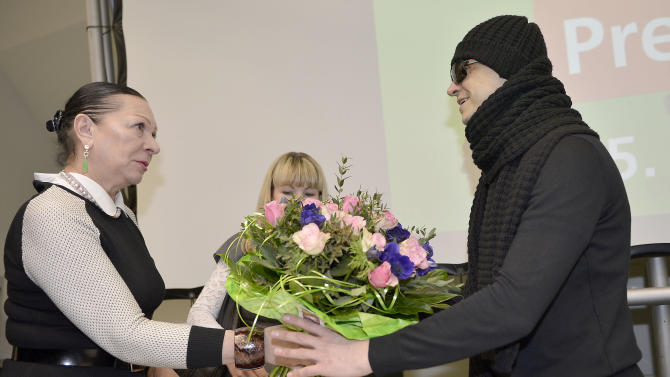 Artistic director of the Bolshoi's ballet troup Sergei Filin, right, receives  flowers from a Russian journalist during a press conference at the university hospital in Aachen, Germany, Friday, March 15, 2013. Filin gets medical treatment in Germany, especially on his eyes, after he was attacked with acid in January in Moscow. (AP Photo/Martin Meissner)