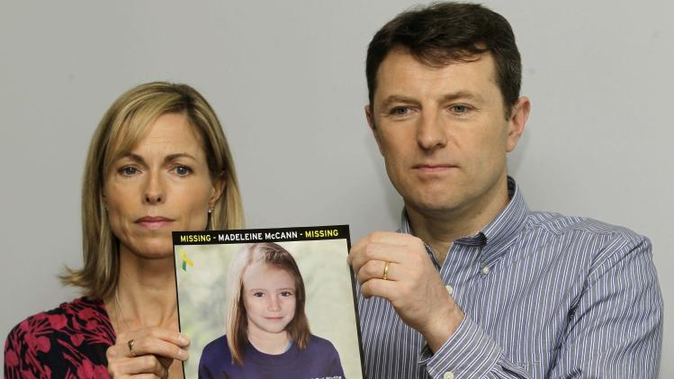 FILE - In this May 2, 2012 file photo, Kate and Gerry McCann pose with a missing poster, an age progression computer generated image of their daughter Madeleine at 9 years old, as they talk to the media in London to mark their daughter Madeleine's birthday and the 5th anniversary of their daughter disappearance during a family vacation in southern Portugal in May 2007 shortly before her fourth birthday. New Zealand police said Wednesday, Feb. 13, 2013 DNA tests have confirmed a New Zealand girl is not missing British youngster Madeleine McCann. (AP Photo/Sang Tan, File)
