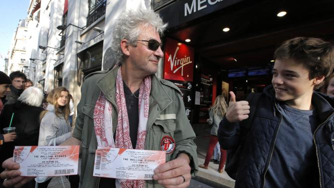 """Rolling Stones fan who named himself Patrice, 55, left, and who claims he has seen 54 Rolling Stones concerts, shows the tickets he bought for Thursday night's concert in Paris, Thursday, Oct. 25, 2012. The Rolling Stones announced a surprise """"warm-up gig"""" in Paris, and within an hour the Champs Elysees was swarming with fans hoping to get satisfaction with one of the 350 tickets for the Thursday night show. (AP Photo/Francois Mori)"""