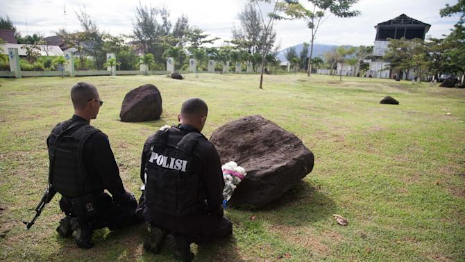 Policemen pray for their dead friends and relatives at a mass grave for victims of the December 26 tsunami in Banda Aceh, northern Sumatra