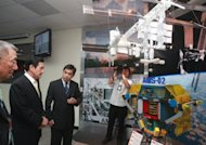 Taiwan President Ma Ying-jeou (2nd L) looks at a model of the Alpha Magnetic Spectrometer II (AMS II) at the Chungshan Institute of Science and Technology. Taiwan opened a space research control centre Tuesday, as part of an ambitious international project aimed at exploring the origins of the universe