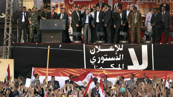 FILE - In this Friday, June 29, 2012 file photo, new Egyptian President-elect Mohammed Morsi gives a speech at Tahrir Square in Cairo, Egypt. Standing before tens of thousands of adoring supporters in Tahrir Square, Morsi opened his jacket to show he is not wearing a bullet-proof vest. The message is clear: He has nothing to fear because he sees himself as the legitimate representative of Egypt's uprising. His speeches reveal a populist bent, making generous promises that many are skeptical he can keep. And though he began as an awkward and uninspiring speaker, he appears to be striving to reinvent his decidedly uncharismatic public persona. (AP Photo/Khalil Hamra, File)