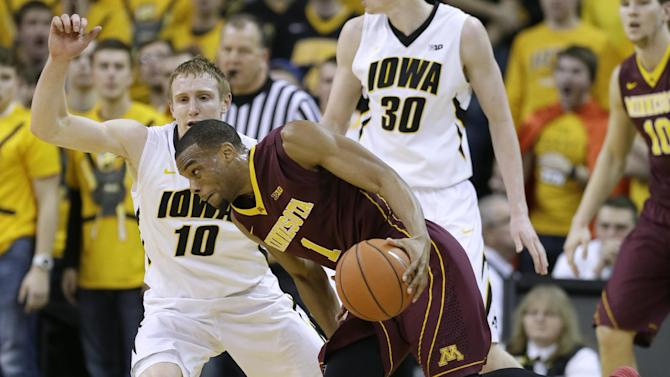 Minnesota guard Andre Hollins, right, drives past Iowa guard Mike Gesell (10) during the second half of an NCAA college basketball game, Sunday, Jan. 19, 2014, in Iowa City, Iowa. Iowa won 94-73