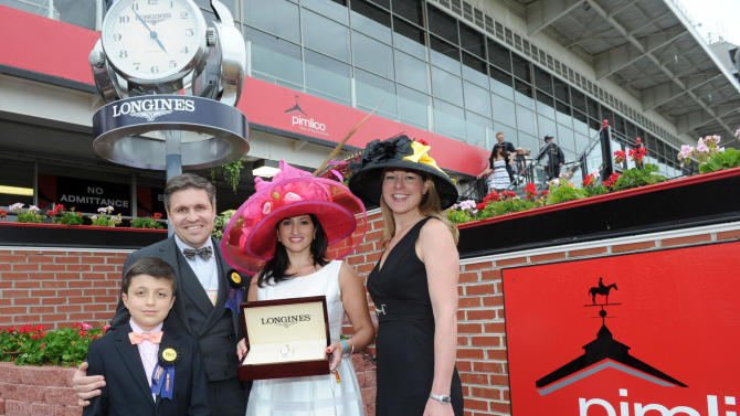 IMAGE DISTRIBUTED FOR LONGINES - Juan-Carlos Capelli, left, with his son Thomas, and Jennifer Judkins, right, both of Longines, present Holly Huff, of Crofton, MD, with a Longines St. Imier steel and rose gold diamond timepiece after she won the Longines Most Elegant Woman at Preakness Fashion Contest, Saturday, May 18, 2013, at Pimlico Race Course in Baltimore, MD.  Longines, the Swiss watch manufacturer known for its luxury timepieces, is the Official Watch and Timekeeper of the 138th annual Preakness Stakes. (Diane Bondareff/Invision for Longines/AP Images)