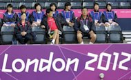 North Korea's coach Gun Sin Ui (C) waits for his team's delayed group G women's match against Colombia to start in the football competition in the London 2012 Olympic Games at Hampden Park, Glasgow, Scotland. The Olympic Games women's football match between North Korea and Colombia eventually got underway on Wednesday after an hour's delay caused by an embarrassing mix-up over national flags