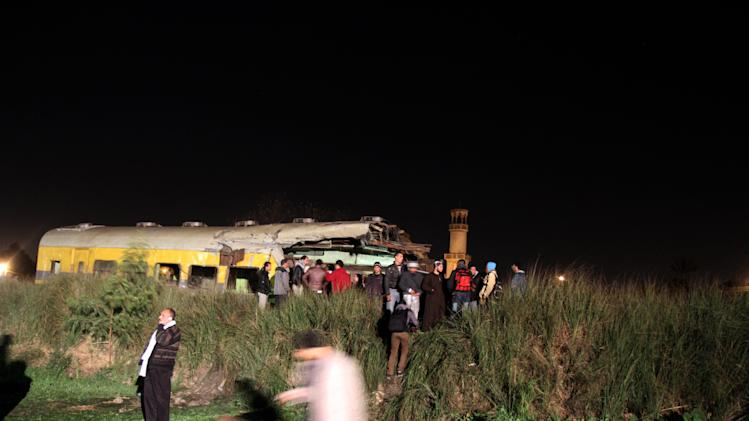 Egyptians try to help rescue injured passengers following a train crash in Badrasheen, 40 KM south of Cairo, Egypt, Tuesday, Jan. 15, 2013. At least 19 people died and more than 100 were injured when two railroad passenger cars derailed just south of Cairo, health officials say. The accident comes less than two weeks after a new transportation minister was appointed to overhaul the rail system, and just two months after a deadly collision between a train and school bus. (AP Photo/Ahmed Gomaa)