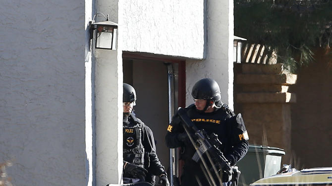 Members of the Phoenix Police Department SWAT team exit the garage at the home of a suspected gunman who opened fire at a Phoenix office building, wounding three people, one of them critically, and setting off a manhunt that led police to surround his house for several hours before they discovered he wasn't there, Wednesday, Jan. 30, 2013, in Phoenix.  Authorities believe there was only one shooter, but have not identified him or a possible motive for the shooting. They don't believe the midmorning shooting at the complex was a random act. (AP Photo/Ross D. Franklin)