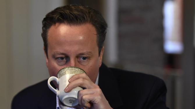 Britain's Prime Minister David Cameron enjoys a hot drink while he visits local members of the farming community during a campaign visit at Whole House Farm, near Brecon in Wales