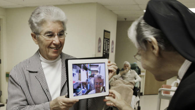 In this April 10, 2012, photo, sister Priscille Roy, left, holds up an iPad displaying her colleague, Sister Pauline Demers, who is in Brazil, to show Sister Elaine Lachance, right, at St. Joseph Convent in Biddeford, Maine. Good Shepherd Sisters of Quebec has just six convents in Maine and Massachusetts with fewer than 60 sisters. The youngest is 64, and it's been more than 20 years since a new member has joined. Sister Lachance is using the Internet, social media and even a blog to attract women who feel the calling to serve God. (AP Photo/Pat Wellenbach)