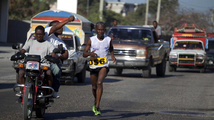 "In this Jan. 6, 2013 photo, Astrel Clovis, a 42-year-old marathon runner, competes in the ""Let's Go Haiti,"" race, organized in honor of those who died in the 2010 earthquake,  Clovis has run the hills and streets of Port-au-Prince for the past 10 years. He decided to take the sport seriously after he entered a race in downtown Port-au-Prince on a whim - and won. In a country where good health is a luxury, running keeps Clovis strong. He clocks about 75 miles (120 kilometers) a week. (AP Photo/Dieu Nalio Chery)"