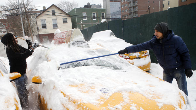 Shaon Chowdhury, right, manager of Arthur Cab Leasing Corp., and employee Kyle Hinkson, of Harlem, clear snow from a taxi while preparing to put it back into service following a winter storm, Tuesday, Jan. 27, 2015, in the Queens borough of New York. Chowdhury estimates that the winter storm has cost his company approximately $60,000 in lost revenue and added expenses. (AP Photo/Jason DeCrow)