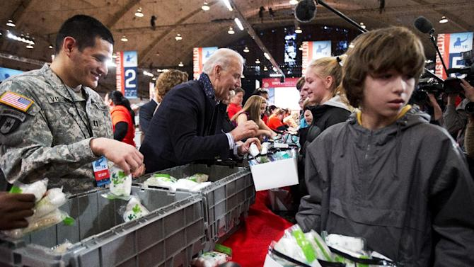 Vice President Joe Biden, center, fills care kits with necessities for deployed U.S. service members, wounded warriors, veterans and first responders, joining the National Day of Service as part of the 57th presidential inauguration in Washington, Saturday, Jan. 19, 2013. Volunteer Nathan Fouse walks with a care kit at right. Army Capt. Cesar J. Visurraga, US Army Nurse Corps, is at left   (AP Photo/Manuel Balce Ceneta)