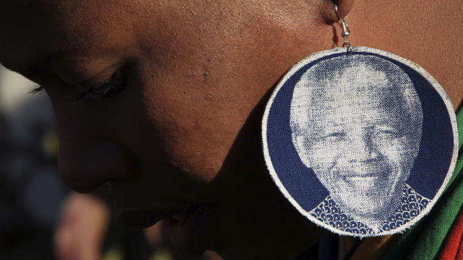 An unidentified woman wearing earrings bearing the image of former South African President Nelson Mandela, outside the Mediclinic Heart Hospital where he is being treated in Pretoria, South Africa, Wednesday, June 26, 2013. South Africa's president Jacob Zuma on Tuesday urged his compatriots to show their appreciation for Nelson Mandela, who is in critical condition in a hospital, by marking his 95th birthday next month with acts of goodness that honor the legacy of the anti-apartheid leader. (AP Photo/Themba Hadebe)