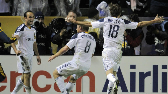 Los Angeles Galaxy forward Landon Donovan, left, celebrates his goal with teammates midfielder Chris Birchall, center, and forward Mike Magee during the second half of their MLS Cup championship soccer match against the Houston Dynamo, Sunday, Nov. 20, 2011, in Carson, Calif. The Galaxy won 1-0.  (AP Photo/Mark J. Terrill)