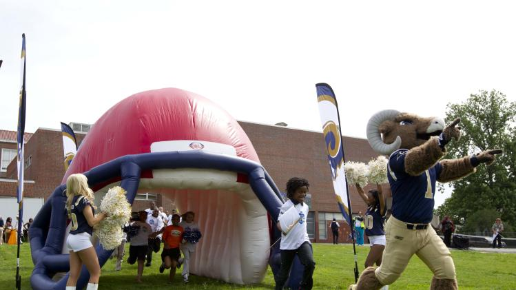 In this photograph taken by AP Images for NFL Network, St. Louis Rams cheerleaders, the Rams' mascot, Rampage, and Leon at Blow K-8 School students run onto to the field during an NFL Network Keep Gym in School minicamp Tuesday, May 8, 2012 Leon at Blow K-8 School in St. Louis. NFL Network, Charter and the St. Louis Rams donated $25,000 to the school's physical education department as part of the program's initiative to ensure quality physical education in America's middle schools. (Whitney Curtis /AP Images for NFL Network)