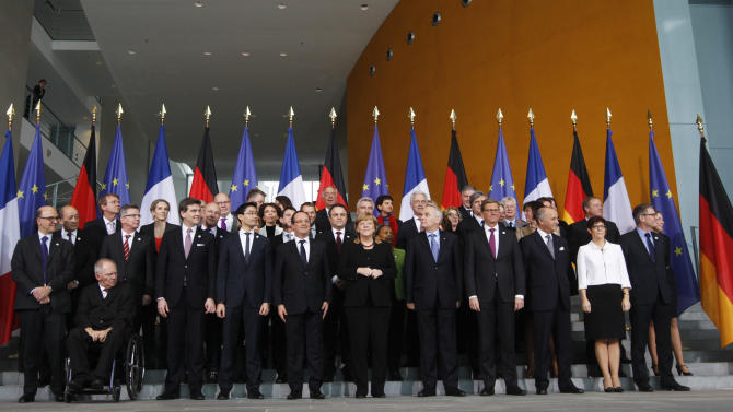 French President Francois Hollande, center left, and German Chancellor Angela Merkel, center right, pose with their governments for a group photo at the chancellery in Berlin, Germany, Tuesday, Jan. 22, 2013. The governments meet as part of events marking the 50th anniversary of the signing of the Elysee Treaty, a landmark accord cementing reconciliation between the two European powers. (AP Photo/Markus Schreiber)