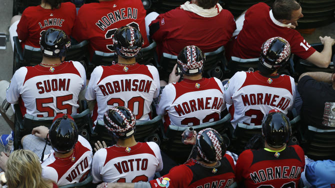 Canada baseball fans wear hockey helmets as they watch Canada play the United States in the fourth inning during a World Baseball Classic baseball game on Sunday, March 10, 2013, in Phoenix. (AP Photo/Ross D. Franklin)