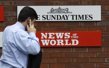 A man passes a sign outside the News International Limited complex, in London