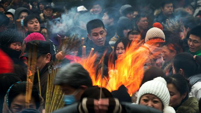 Chinese burn incense as they pray for health and fortune on the first day of the Lunar New Year at Yonghegong Lama Temple in Beijing Sunday, Feb. 10, 2013. Millions across China are celebrating the arrival of the Lunar New Year, the Year of the Snake, marked with a week-long Spring Festival holiday. (AP Photo/Andy Wong)