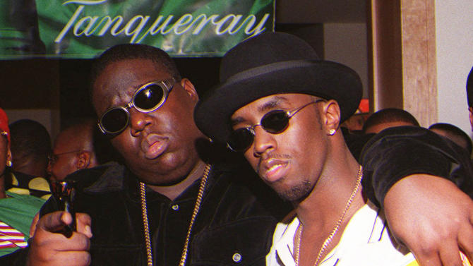 """**FILE**In this March 8, 1997 file photo, Notorious B.I.G., whose real name is Christopher Wallace, left, gestures as he and producer Sean """"Diddy"""" Combs leave a party at the Petersen Automotive Museum in Los Angeles late Saturday evening, shortly before Wallace was shot to death. Authorities have unsealed an autopsy report the week of Nov. 26, 2012 showing that rapper Notorious B.I.G. was shot four times in a 1997 drive-by shooting that remains unsolved. (AP Photo/Venus Bernardo-Prudhomme, File)"""