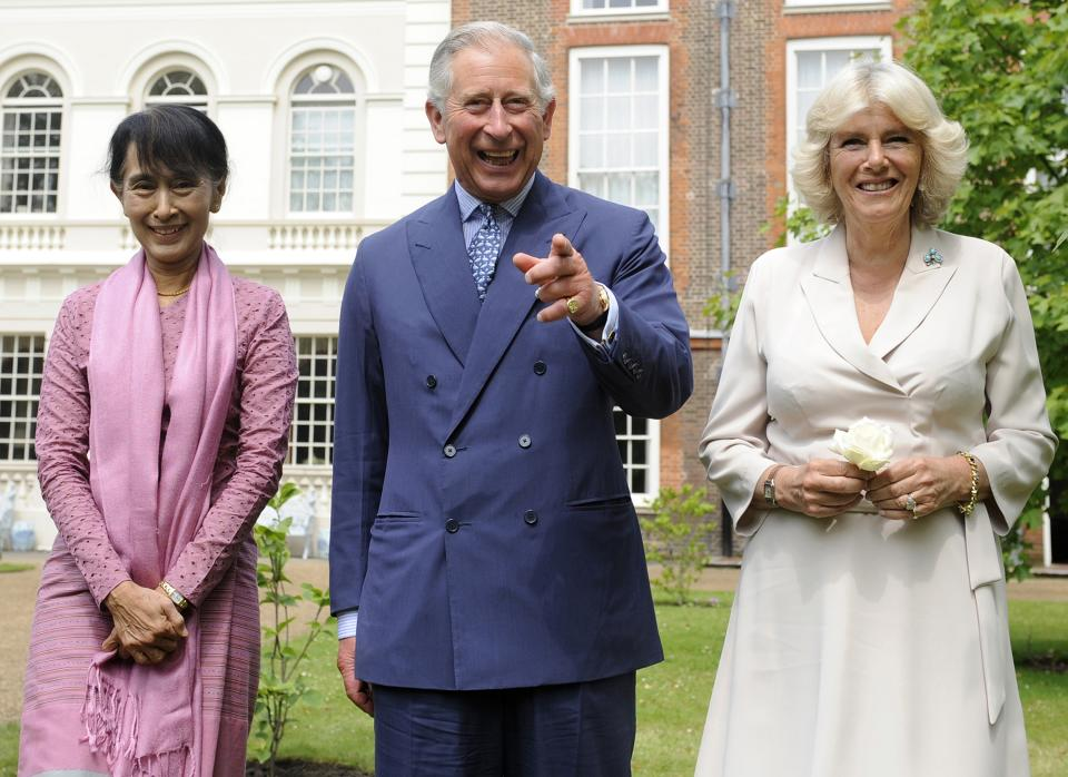FILE - In this June 21, 2012 file photo, Myanmar opposition leader Aung San Suu Kyi, left, Britain's Prince Charles, center, and Camilla Duchess of Cornwall react after planting a Magnolia tree in the gardens of Clarence House, in London. (AP Photo/Facundo Arrizabalga, Pool, File)